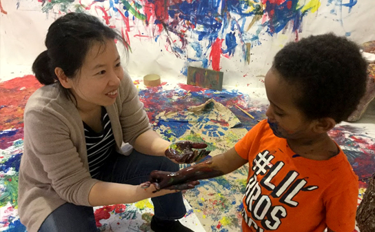 A Photo of an educator and child sharing paint from one of their hands to the other in a room where the walls and floor are covered in white paper that has multicolored paint all over it