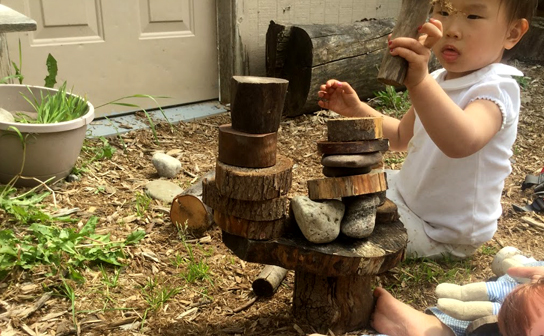 A photo of a child kneeling on woodchips stacking a variety of cut tree cookies and stones into a uniquely shaped structure