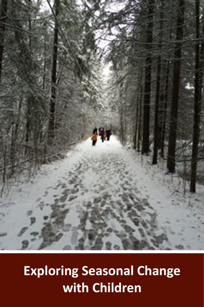 """Webinar title written in white on a brown background reads """"Exploring Seasonal Change with Children"""". Above is a photo of a snowy pathway with people walking down it in the distance. The wide path is surrounded by snow covered trees on either side"""